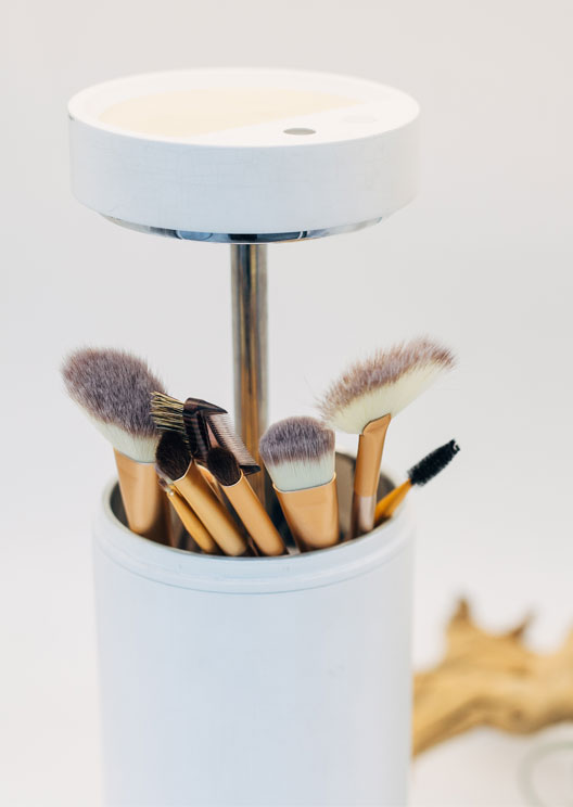 This high-tech brush holder cleans your makeup brushes using UV light
